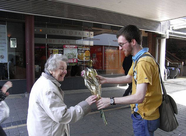 Gent handing flowers to elderly lady. Kindness