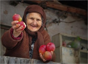 A Romanian villager sharing a few apples from her garden.