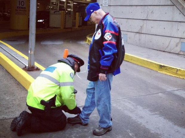 Policeman Tying an Old Man's Shoes
