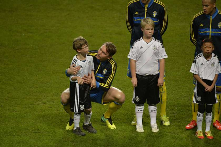 A member of the Swedish national team consoles a frightened autistic child at a game against Germany