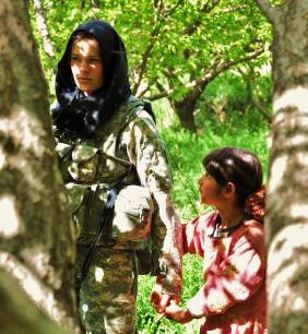 A young Afghani girl being helped by an American female soldier