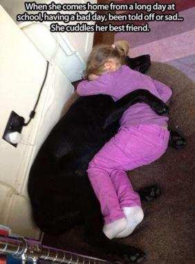 little girl cuddling her dog