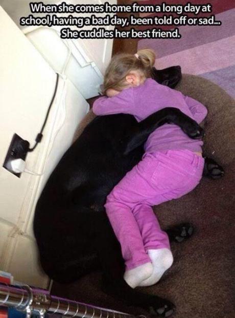 little girl cuddling her dog