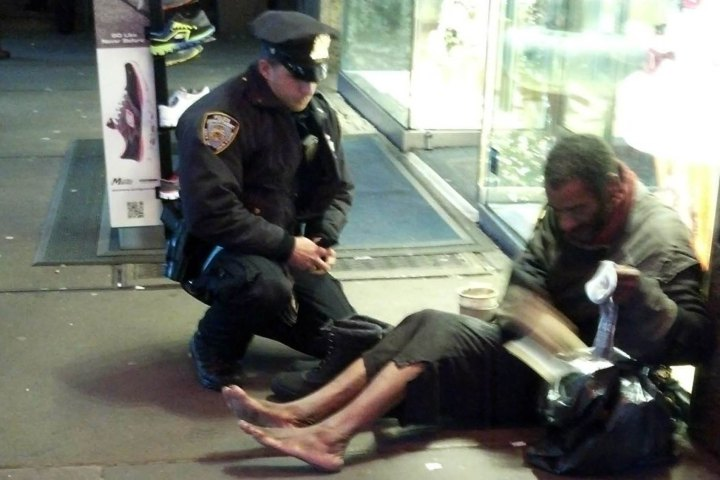 New York City Police Officer Larry DePrimo presenting a barefoot homeless man in New York's Time Square with boots