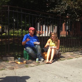 girl sits down with a homeless man and gives him a meal