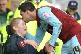 The photo shows, footballer, Danny Ings or Burnley FC presenting a young Clarets fan, 13-year old Joseph Skinner, with his boots after the game .