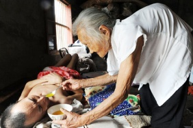 A 97 year old Chinese mother feeding and taking care of her 60 year old paralyzed son every day for over 19 years