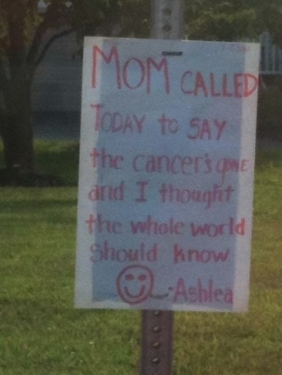 girl writes a sign to celebrate her mum getting the all clear from cancer