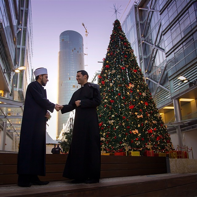 islamic imam and christian priest shaking hands