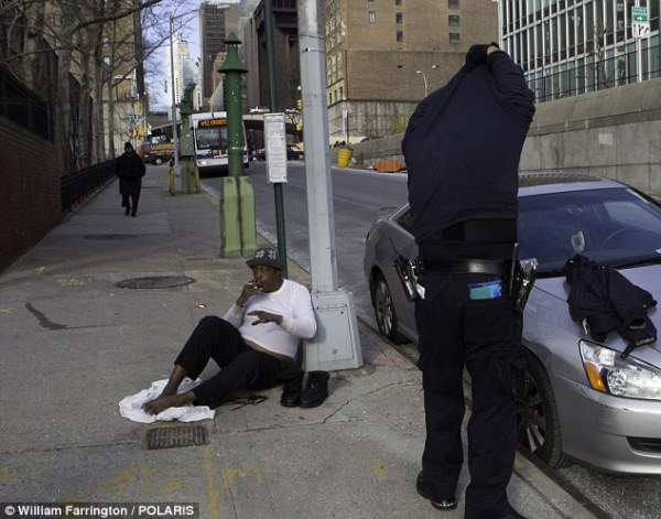 Warm heart: NYPD Transit Bureau officer Carlos Ramos stopped and gave Robert William a sweater off his back in the frigid New York morning on Friday