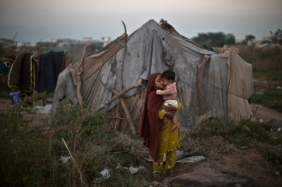 A Pakistani girl comforts her brother near her family's makeshift tent in a slum in Islamabad, Pakistan, Monday, Oct. 21, 2013. Slums, which are built on illegal lands, have neither running water or sewage disposal. (AP Photo/Muhammed Muheisen)
