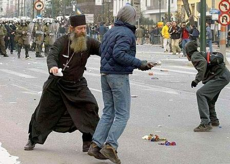 Photo of a priest attempting to stop a rioter from throwing a molotov cocktail at riot police