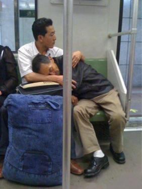 old man sleep on young man on the subway - kindness