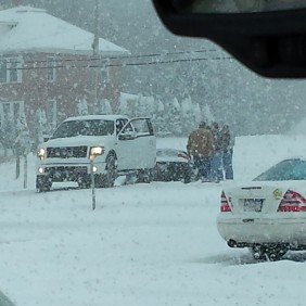 men helping people and cars stuck in the snow