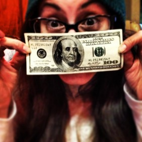 girl holds up a 100 dollar bill which was a tip from a stranger - kindness