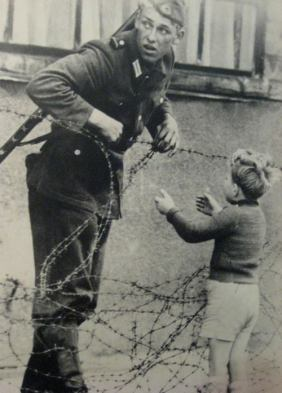 An East German soldier helps a young boy cross the barbed wire which was a marker for where the Berlin wall would soon be built. The guard was caught and immediately punished (which we can assume was by death) So sad.