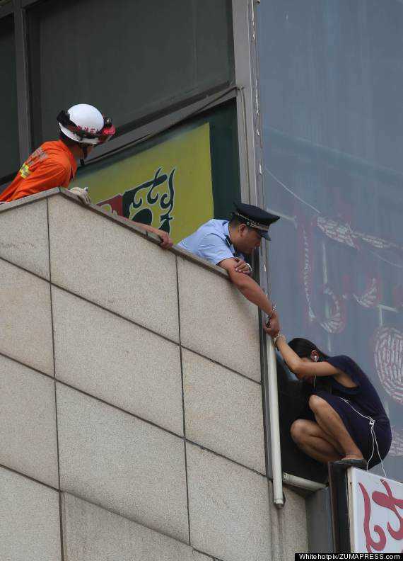 With only seconds to spare, a resourceful Chinese cop figured out how to rescue a suicidal woman dangling precariously from a ledge.  Authorities were called to the heart-pounding scene in Sanlitun in Beijing on Wednesday after a woman climbed to the top of a billboard and appeared to be prepared to jump, according to ZUMA Press, an independent photo agency that released the dramatic images.