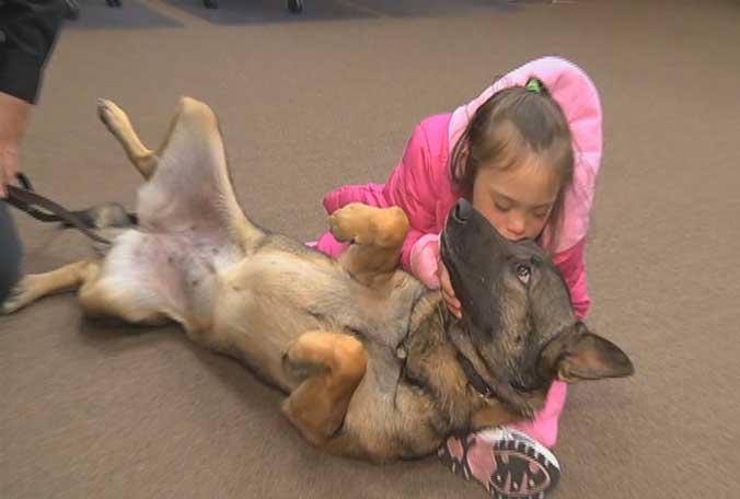 Elina gives her new friend Echo, a 2-year-old German shepherd, a kiss.