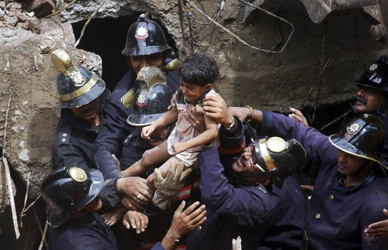 Rescue workers carry a child who was rescued from the rubble at the site of a collapsed residential building in Mumbai, India, in September.