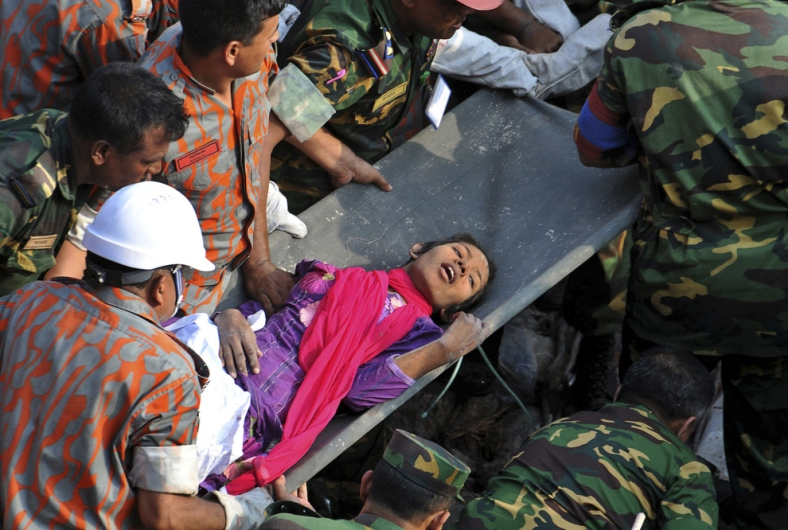 Rescuers pull out a female survivor, Reshma, alive 16 days after a garment factory building collapsed in Bangladesh.
