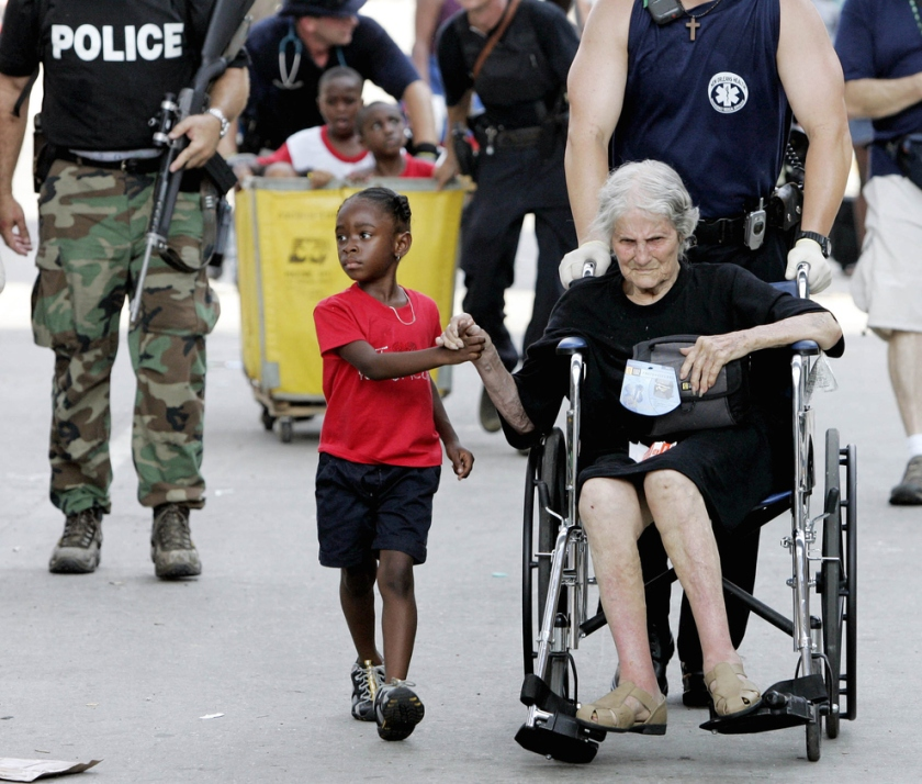 Tanisha Blevin, 5, holds the hand of fellow Hurricane Katrina victim Nita LaGarde, 105, as they are evacuated from the convention center in New Orleans