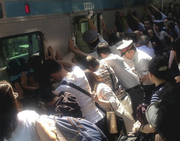 Train passengers and railway staff push a train car to rescue a trapped woman at Minami Urawa station. Photograph: Norihiro Shigeta/AP Dozens of Japanese commuters pushed a 32-tonne train carriage away from the platform to free a woman who had fallen into the 20cm (8in) gap between it and the platform. The act of collective heroism was captured by a newspaper photographer. A public announcement that a passenger was trapped prompted about 40 people to join train officials to push the carriage, whose suspension system allows it to lean to either side, the Yomiuri newspaper reported. The unnamed woman in her 30s was then pulled out uninjured to applause from onlookers at JR Minami-Urawa station, just north of Tokyo. After just an eight-minute delay, the train went on its way.