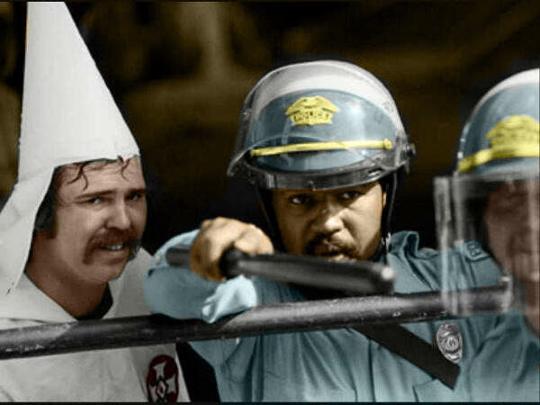 1983 – Austin, Texas.This policeman protects KKK members during a rally as protestors were closing in on them.