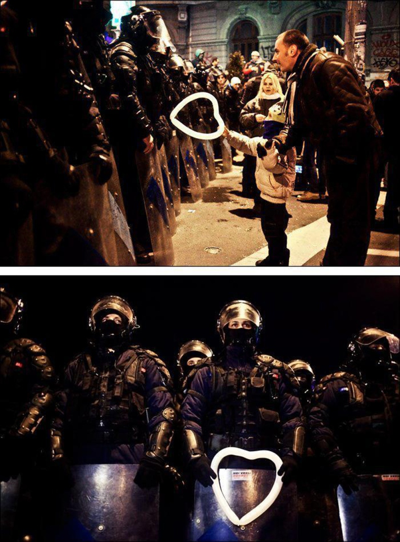 A Romanian child hands a heart-shaped balloon to riot police during protests against austerity measures in Bucharest.