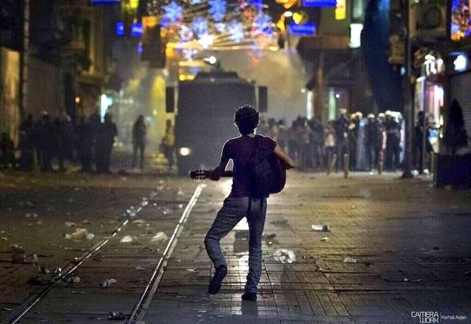 A Turkish protestor plays guitar for police [Turkey, 2011]