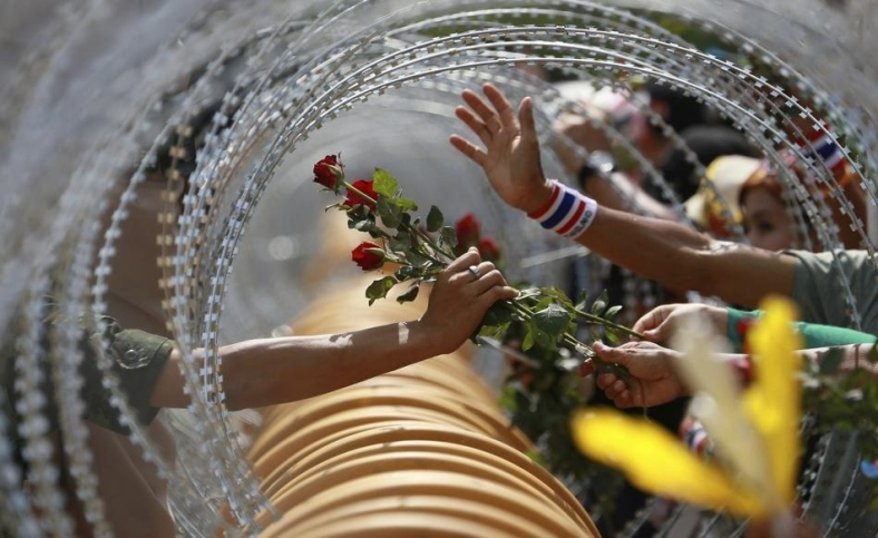 An anti-government protester gives a rose to a Thai soldier at the Defense Ministry during a rally in Bangkok.
