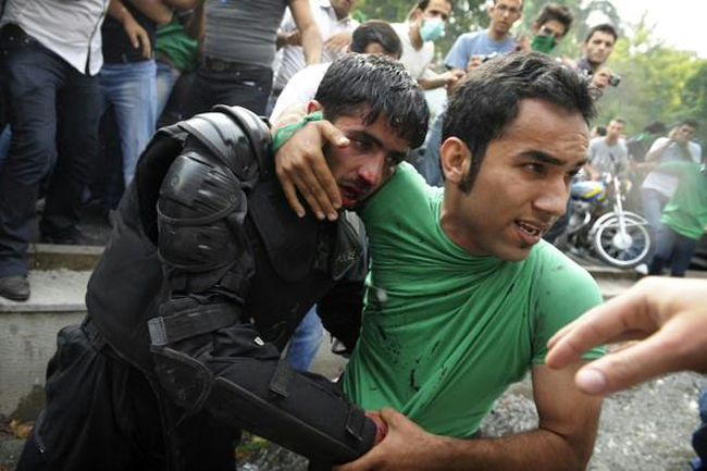 An Iranian police officer is protected by civilians after being beaten by rioters [Tehran, Iran, 2009]