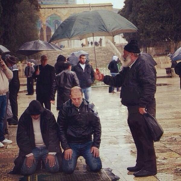 man holds umbrella over two men praying