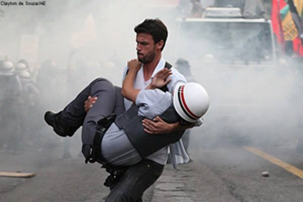 Brazilian protester carrying an injured officer to safety [Sao Paulo, Brazil, 2012]