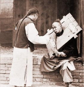Charitable Chinese man feeding a criminal in a cangue. Petty criminals were sentenced to wear the canque, often for a couple of months, and display themselves in public places.
