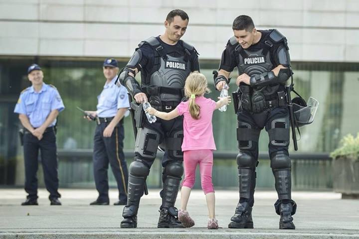 Girl hands water to two officers [Bosnia, 2013]
