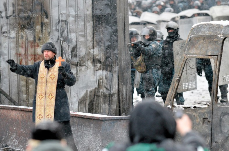 Jan. 22, 2014 – An Orthodox priest tries to stop a clash between protesters and the police in the center of Kiev, Ukraine.