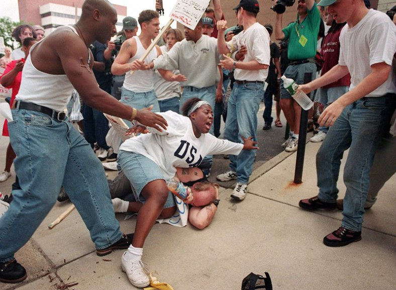 June 22, 1996 – Then 18-year-old Keshia Thomas of Ann Arbor shields a man wearing a Confederate T-shirt from an angry crowd during a Ku Klux Klan rally outside Ann Arbor's city hall.