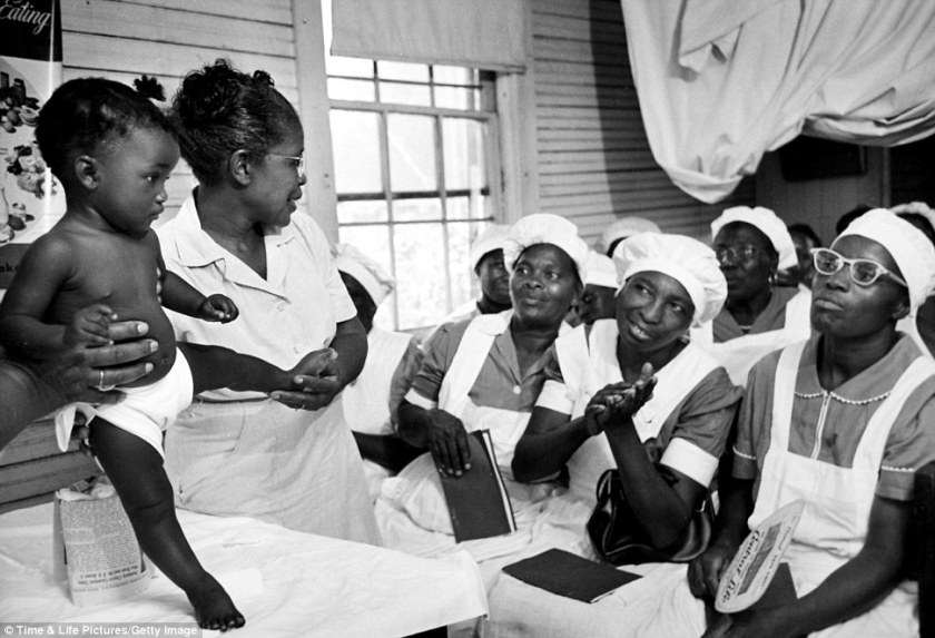 Maude Callen (left) holds a baby as she teaches midwifery students how to look for abnormalities