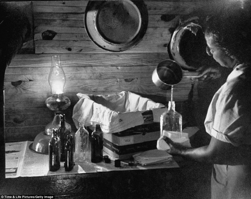 Maude Callen preparing a solution in front of an incubator made from a box and whiskey bottles full of warm waterRead more