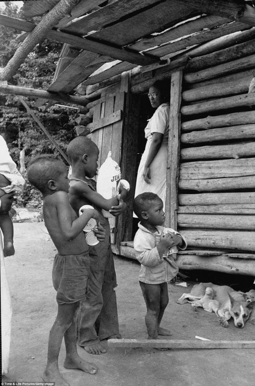 Store bought food donated by Maude Callen, standing in doorway, fascinates youngsters outside a log cabin