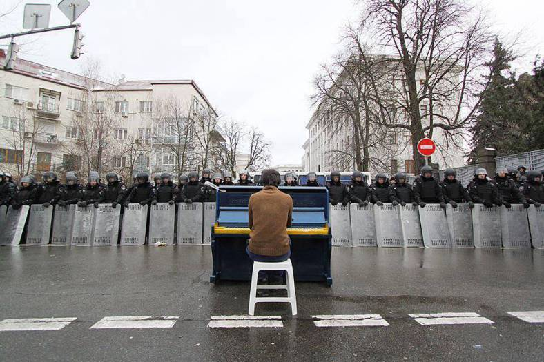 Man sits playing piano to riot police. Ukraine – December 2013