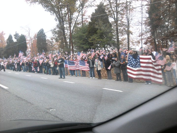 Mourners form a 5-mile barrier between a soldier's funeral and the Westboro Baptist Church [USA, 2012]