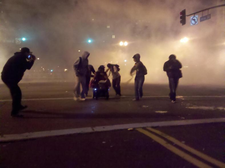 Occupy protesters help a woman in a wheelchair escape teargas [Oakland, USA, 2011]