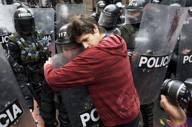 Page by Andrew Boyd  Bogota, Colombia A demonstrator embraces a riot police officer during a student protest against government plans to reform higher education.