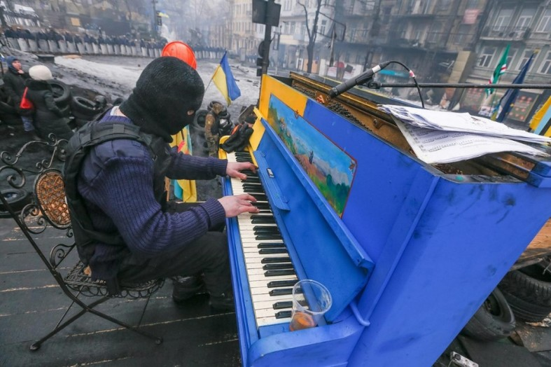A Ukrainian protester plays piano on a barricade in front of the riot police line, Monday, Feb. 10, 2014