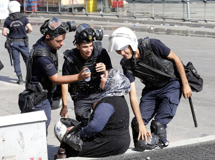 Riot police help a woman affected by tear gas [Ankara, Turkey, 2013]