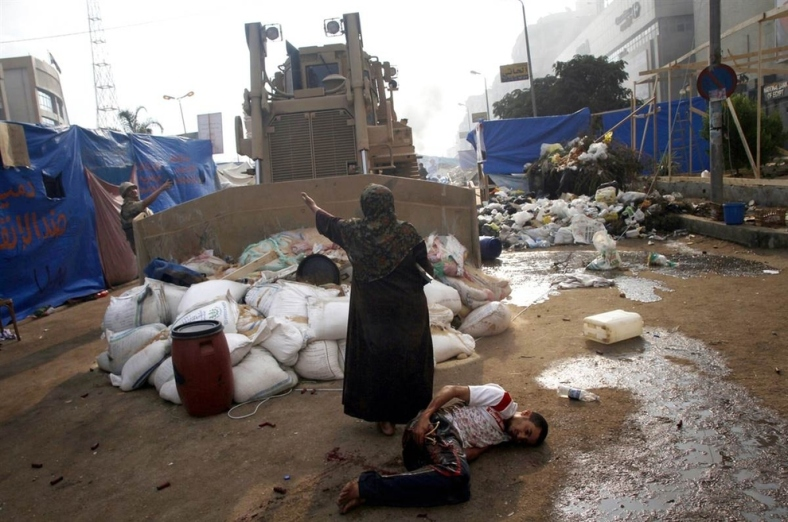 Woman defends a wounded protester from a military bulldozer [Egypt, 2013]