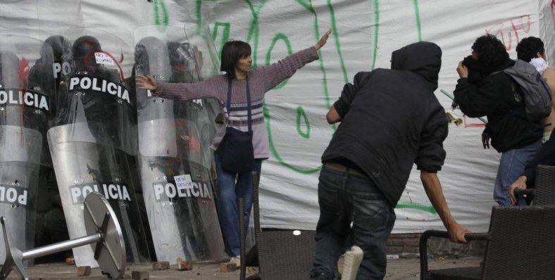 Woman successfully defends a group of cornered riot officers from angry protesters [Bogotá, Colombia, 2013]