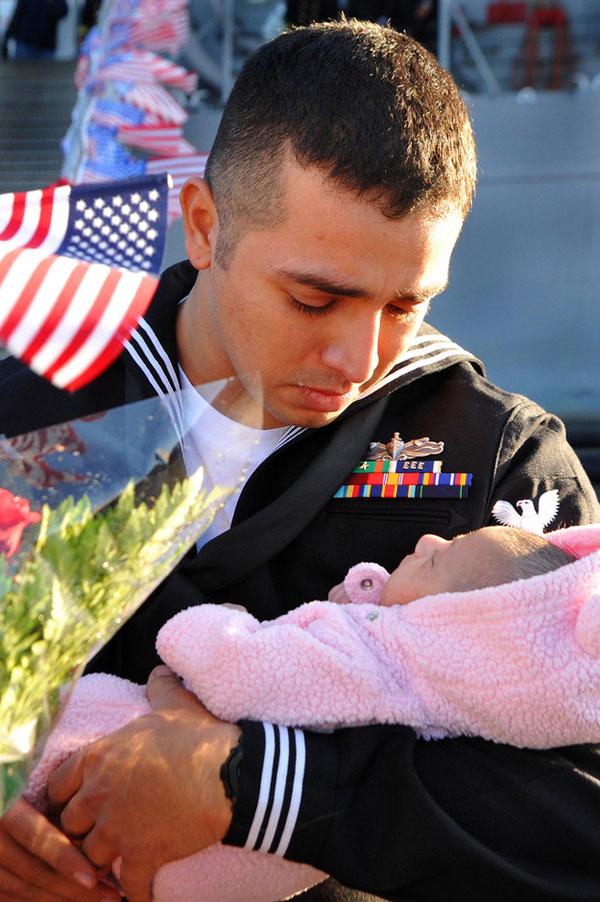 Sailor Stuardo Juarez meets his infant daughter.