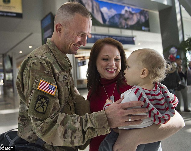 Terminal 5 of the International Airport as a delighted Brandon held his son for the first time. First meeting: Sgt Brandon Niles meets his son, Braedo